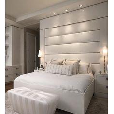 """Um quarto """"All White"""" para uma noite de sono muito tranquila. A cabeceira estofada alta foi emoldurada por moldura em madeira laqueada."""