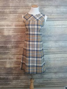 This sheath dress is the perfect everyday dress for the vintage lover, or as a part of a 1950s homemaker Halloween costume. There is no fabric tag, but it feels like wool. Only the top part is lined, but the bottom is unlined. The plaid pattern has blue, tan, and orange. There appears to