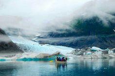 Un bote en el río con montañas, nieve y neblina