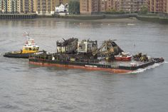 Tug 'SWS Breda' pushes barge 'Battersea Power' carrying old cranes from the power station out of London.