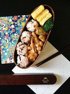 Japanese box lunch, Bento お弁当 Looks like rice balls and tamagoyaki and some kind of chicken.