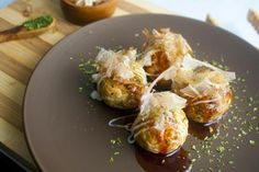 Takoyaki, is a Japanese snack food (street food), which is a grilled pancake in the shape of a round ball with a piece of octopus in a soft center.