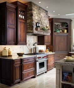 Beautiful wood cabinets, great looking range hood with the stone, and what an amazing range cooker. must have these for my kitchen!!