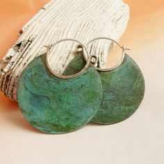 A mottled verdigris patina on our large earth goddess hoop earrings of bronze and sterling silver offer up beautiful color on these unique and rustic
