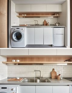 The kitchen in this tiny apartment, has a small cooktop, mini-fridge, washer/dryer and some storage.