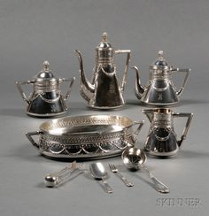 Cased Faberge Silver Nine Piece Tea, Coffee and Dessert Set, Moscow, 1908-17, Classical Revival styling, comprising tapered conical teapot, coffeepot, covered sugar and creamer, with reeded angular handles, engraved diagonal guilloche and husk neck band, applied with ribbon-tied husk swags to body, domed lids with inverted berry finials, coffeepot, oval bowl, sugar sifting spoon, a sugar shovel, a pair of sugar tongs, and a small berry fork.