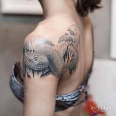 grey snake tattoo on the shoulder