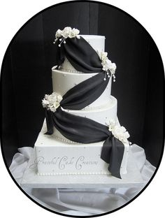 Black and White Wedding Cake with draping black icing and florals.