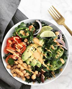 Mediterranean-inspired salad made with base of massaged kale + chickpeas + olives + avocado + cucumber ribbons + tomato + cilantro + red onions + sesame seed + jalepenos + a spicy hummus sauce.