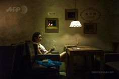 A woman smokes a cigarette in a bar in Beijing on May 27, 2015. Photo @freddufour_afp