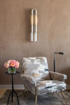 To create a glam moment that doesn't upstage the bedroom's coziness, Korban upholstered a vintage chair from Flair in New York with deconstructed Dedar fabric. An Apparatus Studio sconce doubles as artwork above a task lamp from Vaughan Designs and a side table by Liaigre.