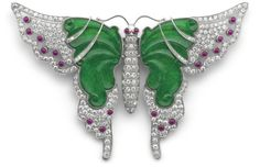 Jade diamond and ruby butterfly pin with outer wings pavé-set with brilliant-cut diamonds and ruby cabochon highlights throughout, to carved jadeite inner wings set with diamond highlights, detachable pin fitting, French assay marks for platinum and gold, wingspan 9.5 cm, length 6.5 cm, fitted case.
