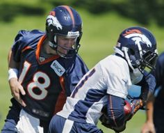 Denver Broncos quarterback Peyton Manning hands the ball off to running back Ronnie Hillman, right, during off season training camp at the NFL football team's training facility in Englewood, Colo., on Thursday, June 6, 2013. (AP Photo/Ed Andrieski)