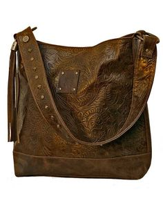 """This tooled metallic leather tote has a magnetic closure, fringe detail and antiqued studding. Dimensions: 12"""" W x 12"""" H x 1.75"""" D Full grain tooled leather Hand-rubbed metallic finish Antiqued hardware and studding  