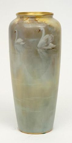 Worcester porcelain vase finely painted with a scene showing swans on a lake in autumnal hues.