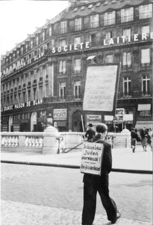 """Paris, France, A man carrying an antisemitic sign which reads: """"In this local (pub, restaurant) jews are unwanted - clean aryan business, 1940""""."""