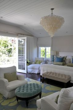 Gorgeous blue & green bedroom design with gray walls paint color, white capiz chandelier, beadboard ceiling, white tufted bed, tan tufted bench, white slip-covered chaise lounge, French doors, green & blue rug, white slip-covered chairs, blue velvet oval ottoman, blue gourd lamp, green bolster pillows and blue & green pillows.