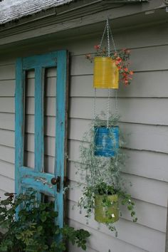 Tin can vertical plant hanger and rustic painted wooden screen door.  Love the screen door as a decorative element with potted plants surrounding.