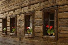 Flower on the window of an very old wooden cottage (Roznov pod Radhostem, Czech Republic) Stock Photo
