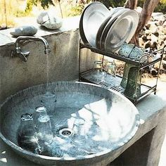 Galvanized outdoor sink mounted on concrete counter outside.