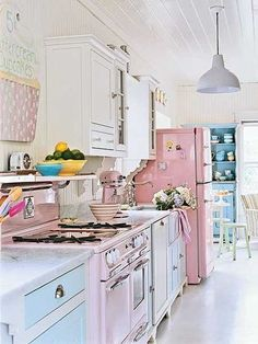 I love how light the colors of this kitchen are--the pink fridge and even lighter pink stove and the white and light blue cabinets...
