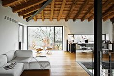 This modern home in Northern Italy matches warm colors of dark wood with the sleek minimalism of white seating. Near the sofa by Piero Lissoni for Cassina is a Bourgie lamp from Kartell; on the large table, made from old roof beams, is a Taccia lamp from Flos. Photo by Helenio Barbetta.  Photo by: Helenio Barbetta