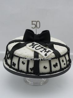 A super stylish present style lady's 50th birthday cake for any woman who likes the contrast of black and white.   This cake has been made to look like a lidded box.  It has tiny small bows and stripes around the bottom half - and an indented square / diamond pattern inlaid with edible sugar pearls on the top half.  It is finished with a stunning big bow, an icing sugar gift tag saying Mum and a beautiful sparkly diamante 50 topper which can be saved as a precious momento of the special day.