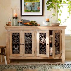 "handcrafted from sustainable, plantation-grown mango wood with a decorative iron grill on four doors. Two fixed shelves. Limed, with water-based stain. Imported. Catalog exclusive. White patina. 64""W x 18""D x 39""H."