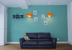 Cool kids room in Bucharest. Blue brick wall with leather sofa and orange lighting