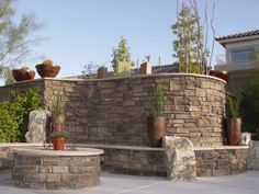 Tuscan Wall  The wall is a smart solution for camouflaging pool equipment and helping to reduce the sound. Silverado Ledgestone with a flagstone cap contributes to the Tuscan look. Image courtesy of Green Planet Landscap