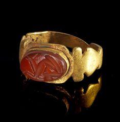 Goldring mit Gemme aus Karneol. Römisch, 2. - 3. Jh. n. Chr. 2,29g, Umfang 44mm. Mit flacher, am Rand profilierter Schiene, auf der Platte in einer Fassung eine querovale Gemme aus rotem Karneol. Darauf ein Hörnertier, das einem Blütenkelch entspringt. Gold! Intakt.  Provenienz: Ex Sammlung R.B., seit den 1990er Jahren.SIXBID.COM - Experts in numismatic Auctions