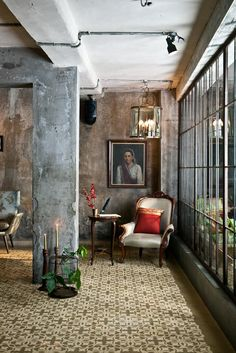 I like the contrast of the concrete with the painting and seating, all of which have a vintage or antique feel.