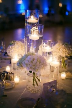 White, Silver & Glass Wedding Inspiration - white flowers, glass cylinders and floating candles. #whitewedding #centerpiece
