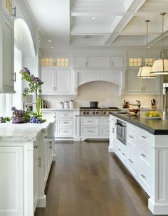 White cabinets, hardwood floors, dark counter, feet on island