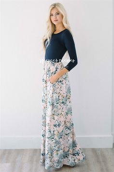 This floral maxi dress is what dreams are made of! Dreamy full length dress features a navy bodice with round neckline and 3/4 length sleeves. Followed by a pale pink and gray floral skirt with cute pockets.