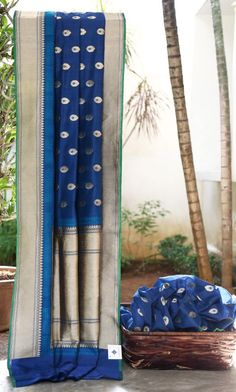 GORGEOUS NAVY BLUE BENARES SILK WITH BLUE AND GOLD BHUTTAS ALL OVER. THE INTRICATELY WOVEN GOLD BORDER AND PALLU GIVE THE SAREE AN EXCLUSIVE FINISH