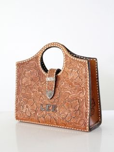 "A vintage tooled leather handbag circa 1950. The thick caramel leather bag features a western floral tooled design with silver metal lettering on the front reading ""LEE"", and white leather top-stitchi"