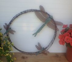 "Metal Dragonfly Barbwire Wreath, Metal Garden Art, Family of Dragonflys Framed in Barbwire size of the whole piece is about 18"" in diameter. The dragonfly's measurements are: 11"" body with a 13"" wing span, 5 1/2 "" body with a 7 1/2"" wing span, and 4 1/2"" body with a 5 1/2"" wing span $48.00 USD Overview Handmade item  Materials: 16 gauge diamond plate metal, 16 gauge sheet metal, 18 gauge expanded metal    Feedback: 309 reviews  Only ships to United States from Princeton, Minnesota."