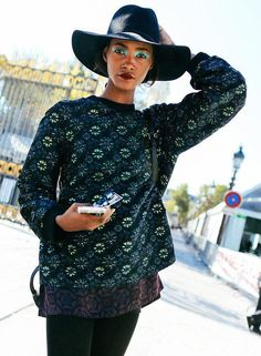 Dries Van Noten sweater, black wide-brimmed hat, statement makeup
