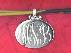 Sterling silver monogrammed pendant hand engraved by Master Hand Engraver, Richard Neustaedter. Call 314-966-4442 to order. This can be shipped throughout the country.
