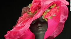 To honor Rapid Reduxs 22 consecutive wins, Steinmann created 22 rose curls to adorn this hat, which utilizes the distinctive pink and yellow racing silks of owner Robert Cole Jr.s racing stable.