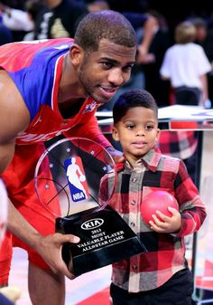 Chris Paul is holding the KIA NBA All-Star MVP trophy with his son Chris Paul ll