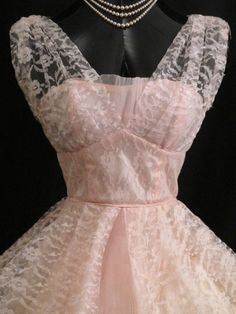 Description  An enchanting original 1950's party dress in a confection of baby pink tulle and lace. The style typifies the 50's - oh so feminine and figure flattering - narrow bodice flaring at the waist. There are three layers to the fabric – a stiff muslin underskirt to give the skirt extra body, a baby pink satin lining, topped with a floating overlayer of baby pink lace backed by tulle. No maker's label remains but this dress appears to have been professionally made. No fabric contents…