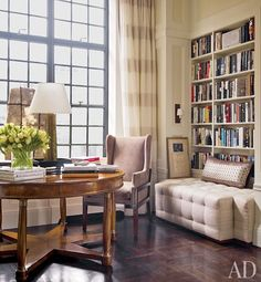 """An Italian Directoire table is paired with a Kaare Klint–inspired wing chair upholstered in an Edelman suede. Holly Hunt linen covers the DKDA-designed """"bookcase sofa,"""" and the curtains are of a Zimmer + Rohde fabric."""