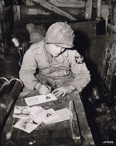 Pvt Walter Prsybyla of B Btry, 37th Field Artillery Regt, US 2nd Inf Div writing Christmas cards for friends and family from an artillery ammunition storehouse, Heckhalenfeld, Germany, 30 Nov 1944. (US Army Signal Corps photo)
