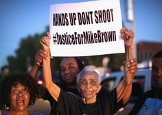 """Demonstrators protesting the killing of teenager Michael Brown in August with the two main slogans """"Hands up, don't shoot"""" and """"Justice for Michael Brown."""""""