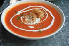Tomato Soup; Heat a large pot over medium-high heat. Pour in oil, then add onion, carrots, garlic, 1 tsp. salt, the red pepper flakes, and bay leaves. Cook, stirring occasionally, until vegetables have softened and onion is translucent, 6 to 8 minutes.  Add tomatoes, crushing them up with your hands, plus their juice and 2 cans water. Bring soup to a simmer and add half of oregano. Decrease heat to very low and simmer, partly covered, 2 hours.