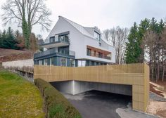 The shingle-clad upper storeys of this house on the outskirts of the Austrian city of Linz by Vienna practice Destilat are rotated to create a cantilevered overhang above the entrance