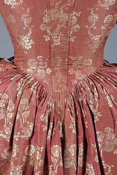 Detail back view open robe and petticioat, 1760s. Dark cinnamon silk brocaded with trails of ivory blooms, with original braid trimmed engageants, 1880s added gold satin trimming; with a quilted pale blue silk petticoat