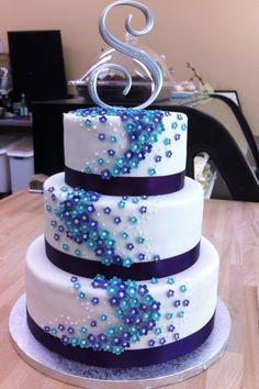 http://fc00.deviantart.net/fs70/i/2012/241/0/8/purple_and_blue_flower_wedding_cake_by_h0p31355-d5cubzh.jpg- Make it a P and put camo around the bottom of each layer and change color of little flowers.. it would be perfect!